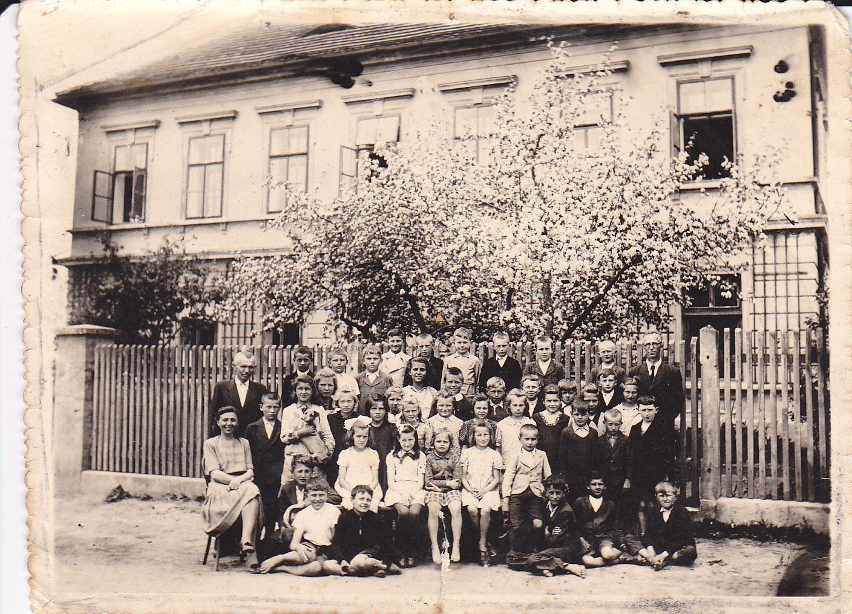 Historická fotografie žáků školy před školou.